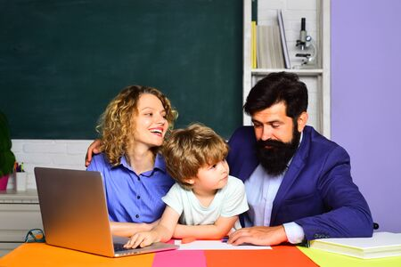Woman and man helps child. First time to school. Parenting. Mathematics for kids. Pupil learning letters and numbers - mathematics concept. Little boy ready to study. Elementary student. Happy family 写真素材
