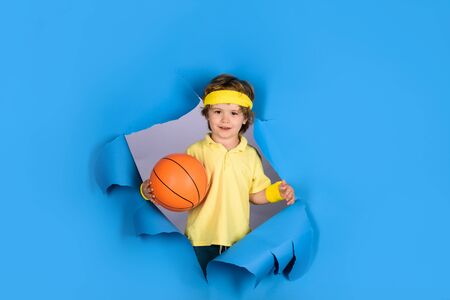 Sports equipment. Happy child boy holds ball shows thumb up. Enjoy sports game. Kid activities. Cute boy playing basketball.