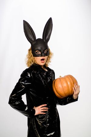 Sexy blonde girl in rabbit black mask with pumpkin. Sexy female model in Easter bunny black rabbit mask with jack-o-lantern.