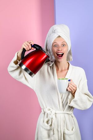 Girl pours water in mug from electric kettle. Happy housewife in bathrobe at home. Smiling woman pours water from kettle into cup. Pretty girl pours hot water from kettle in kitchen. Girl making tea.