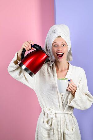 La ragazza versa l'acqua nella tazza dal bollitore elettrico. Casalinga felice in accappatoio a casa. La donna sorridente versa l'acqua dal bollitore nella tazza. Bella ragazza versa acqua calda dal bollitore in cucina. Ragazza che fa il tè.