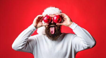 Man in Santa hat covered eyes red Christmas ball. Santa man holds Christmas balls decoration shows tongue. Decor concept. Stock Photo