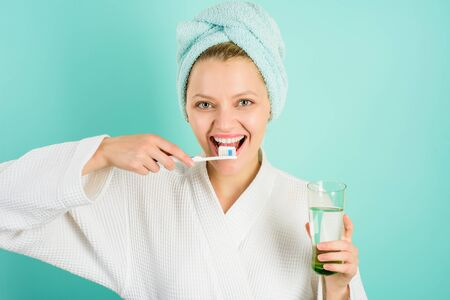 Dental hygiene. Happy woman with towel on head cleaning teeth with toothbrush. Hygienic teeth cleaning every day.
