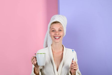 Woman with toothbrush. Morning treatments. Health. Morning. Morning routine. Morning procedures. Awakening. Sleep. Woman with toothbrush and glass of water. Stock Photo