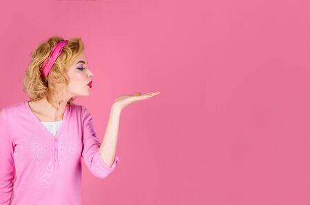 Hautpflege, Haarpflege, Schönheitskonzept. Pin ap Mädchen bläst Kuss aus der Hand. Frau mit perfekter Haut, roten Lippen. Schönes Mädchen, das leeren Kopienraum auf offener Handpalme für Text zeigt. Kopieren Sie Platz für Werbung. Standard-Bild