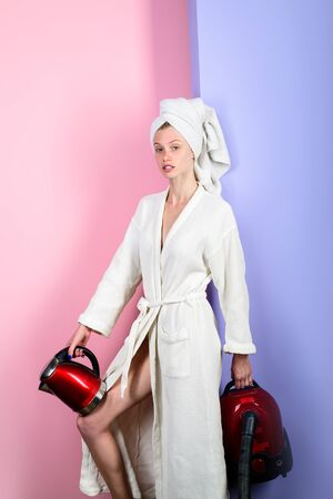 Serious girl in bathrobe and towel on head. Housewife with vacuum cleaner and electric kettle in hands. Busy woman with vacuum cleaner and kettle at home. Sexy woman with vacuum cleaner and teakettle. Banco de Imagens
