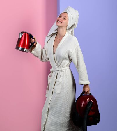 Smiling sexy woman with vacuum cleaner and kettle. Housewife with vacuum cleaner and electric kettle in hands. Woman in bathrobe and towel on head. Happy woman with vacuum cleaner and kettle at home.