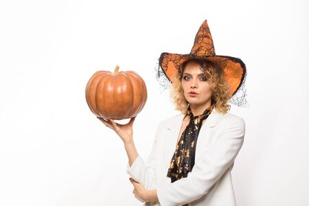 Sexy girl in halloween costume. Witch with pumpkin. Celebration autumn holiday. Trick or treat. Halloween witch in magic hat.