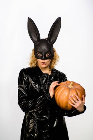 Sexy female model in Easter bunny black rabbit mask with jack-o-lantern. Happy Halloween. Beautiful woman in halloween bunny costume holds pumpkin. Sexy blonde girl in rabbit black mask with pumpkin Stock Photo