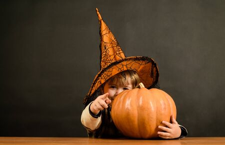 Little boy in witch hat with halloween pumpkin shows finger on you. Trick or treat. Preparation Halloween holiday. Halloween party. Halloween boy pointing to front. Child with pumpkin pointing at you Reklamní fotografie