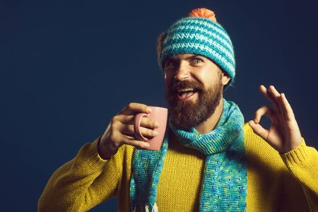 Good morning. Excellent symbol. Happy man shows ok sign. Smiling bearded man with cup coffee.