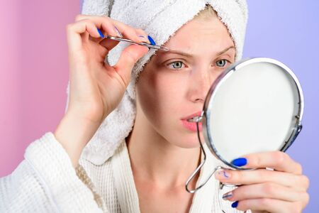 Woman pluck eyebrows looking in mirror. Epilate eyebrows. Woman with tweezers. Girl makeup process. Eyebrows beauty care concept. Beauty tools. Correction procedure in beauty salon.