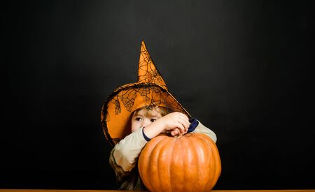 Toddler kid with jack-o-lantern. Trick or treating. Little boy in witch hat with pumpkin. Halloween holidays concept.