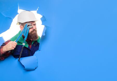 Bearded man with tools in hand. Through paper. Tools or repair service. Worker with pipe wrench. Bearded man in helmet. Uniform. Plumbing and renovation. Bearded man through paper. 写真素材