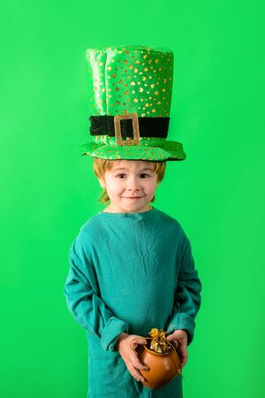 Patrick's Day. Green top hat. Little boy in green hat holds pot with gold. Leprechaun. Coin. Money. Clover. Saint Patrick.Traditions of Saint Patrick Day. Sale. Discount. March. 免版税图像