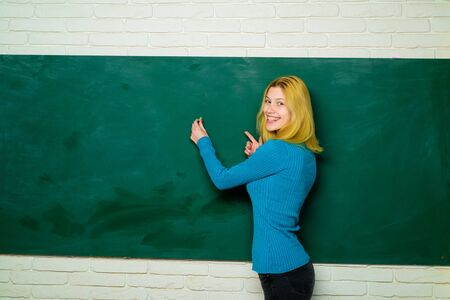 Teacher writing on chalkboard. Education. Teacher in classroom. Job. People concept. Educational theme. Professor educates students. Portrait of teacher near chalkboard. Progressive school.