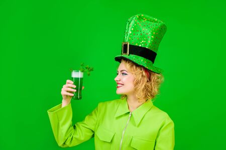 Saint Patrick's Day. Woman in top hat holds glass with green beer. St Patricks Day. Irish beer. Green beer. Green top hat. Green hat with clover. Irish Traditions. Pub. Woman drinking in pub. Isolated.