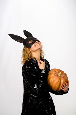 blonde girl in rabbit black mask with pumpkin. female model in Easter bunny black rabbit mask with jack-o-lantern. Beautiful woman in halloween bunny costume holds pumpkin. Happy Halloween