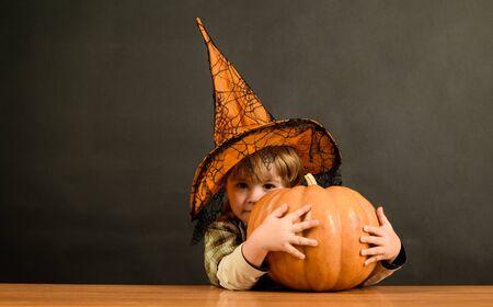 Niño con sombrero de bruja con calabaza. Concepto de vacaciones de Halloween. Feliz Halloween. Niño divertido con sombrero de bruja para Halloween con calabaza Jack. Niño pequeño con jack-o-lantern. Pedir dulce o truco