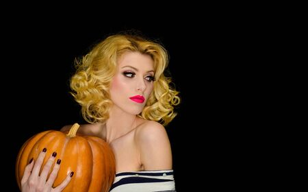 Smiling blond girl with pumpkin. Holidays, decoration, party concept. Jack-o-lantern. Halloween. Trick or treating. Halloween party. Happy Halloween. Woman in witch halloween costume. 31 October Imagens