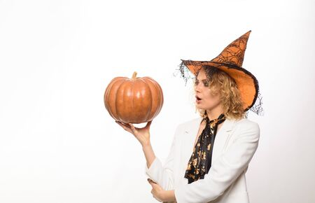 Surprised girl in witch hat with pumpkin. Preparation Halloween holidays. Woman witch with pumpkin. Halloween party. Happy Halloween. Emotional woman in witch halloween costume with jack o lantern