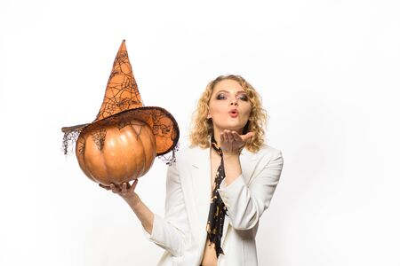 Happy girl with pumpkin blowing air kiss. Preparation Halloween holidays. Woman with pumpkin. Halloween party. Happy Halloween. Emotional woman in witch halloween costume. Traditional holiday symbol Imagens