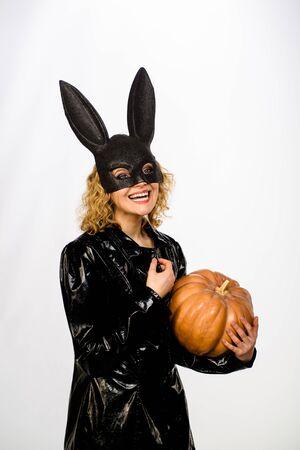 blonde girl in rabbit black mask with pumpkin. Beautiful woman in halloween bunny costume holds pumpkin. Female model in Easter bunny black rabbit mask with jack-o-lantern. Happy Halloween