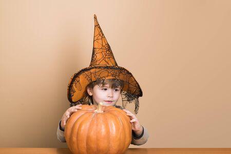 Concepto de vacaciones de Halloween. Feliz Halloween. Niño divertido con sombrero de bruja para Halloween con calabaza Jack. Niño pequeño con jack-o-lantern. Niño con sombrero de bruja con calabaza. Pedir dulce o truco