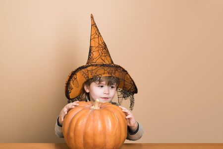 Halloween holidays concept. Happy Halloween. Funny child boy in witch hat for Halloween with pumpkin Jack. Toddler kid with jack-o-lantern. Little boy in witch hat with pumpkin. Trick or treating
