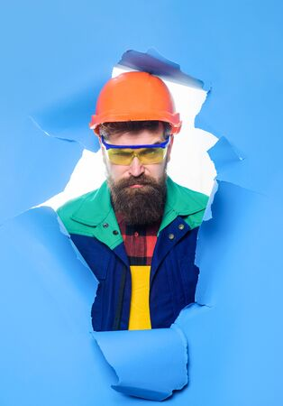 Through paper. Builder in hard hat through hole in paper. Repair. Bearded man in construction helmet. Man in helmet. Construction worker in hardhat. Carpenter. Home renovation.