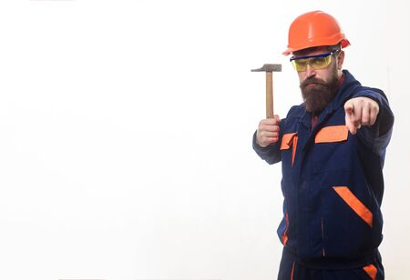 Industrial worker. Engineer. Builder in helmet holds hammer. Mechanic in uniform with hammer pointing at you. Repair service. Handyman with hammer. Construction worker in hardhat pointing to front. Imagens