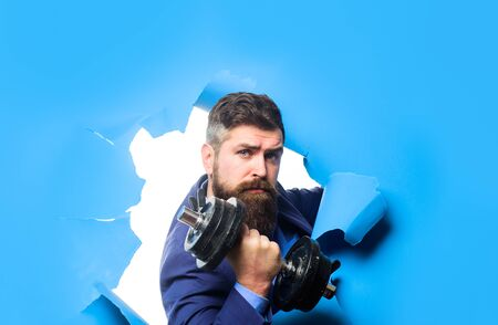 Through paper. Bearded man with dumbbell looking through paper hole. Power. Strength. Bearded man through paper. Workout. Fitness. Healthy lifestyle. Fitness with equipment. Businessman with dumbbell. Imagens