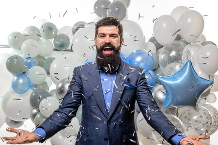 Party man with balloons falling confetti. Birthday man in suit with helium balloons. Celebration, people, holidays, party concept. Smiling man throwing confetti. Happy businessman with flying confetti Stok Fotoğraf