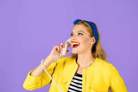 Pinup girl with handset. Smiling woman dressed in yellow jacket holds telephone handset. Happy woman holds handset. Pretty woman talking at retro handset. Girl talking on landline phone. Communication Фото со стока