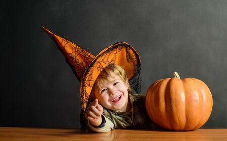 Cute boy in witch hat with halloween pumpkin pointing to you. Kid trick or treat. Halloween party. Boy dressed up trick or treating. Preparation Halloween holiday. Child with pumpkin. Happy Halloween Imagens
