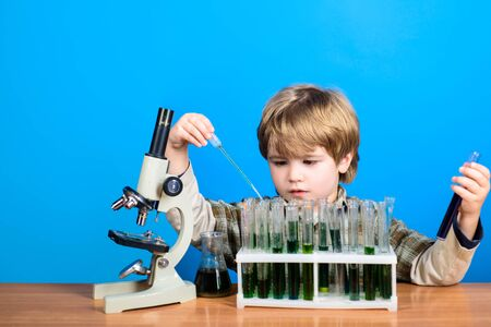Science. Chemistry. Experiment. Education. Study. Smart boy working with microscope and test tubes. Little kid with microscope. Modern technology.