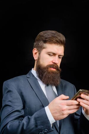 Bearded business man typing message. Sms. Internet. Communication. Successful male entrepreneur using cellphone wireless connection for work. Businessman holds mobile smart phone. Handsome man in suit Zdjęcie Seryjne