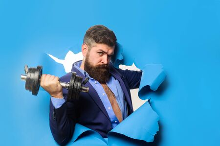 Businessman with dumbbell. Fitness with equipment. Bearded man with dumbbell looking through paper hole. Power. Strength. Zdjęcie Seryjne