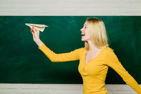 Female student playing paper airplane in classroom. Happy girl throwing paper airplane. Girl near school board with paper airplane.