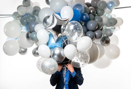 Handsome happy man with big bunch of balloons. Bearded man with balloons at birthday party.