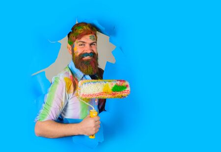 Painter. Through paper. Repair tools. Bearded painter with paint roller. Room painting. Hard hat. Construction. Industrial concept. Repair. Bearded man through paper. Stok Fotoğraf
