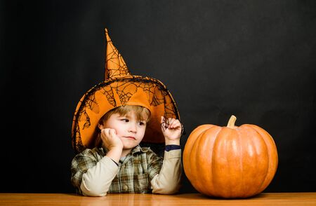 Jack o lantern. Niño con sombrero de bruja con calabaza de halloween. Preparación fiesta de Halloween.