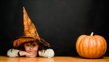 Jack o lantern. Kid in witch hat with halloween pumpkin. Preparation for Halloween party. Boy dressed up trick or treating. Kid with pumpkin.