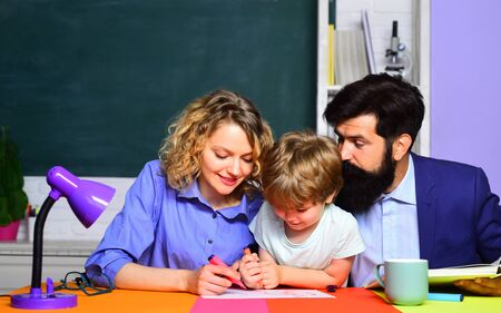School. School boy in first grade. Happy family schooling math together. Cute pupil and his father and mother making homework 版權商用圖片