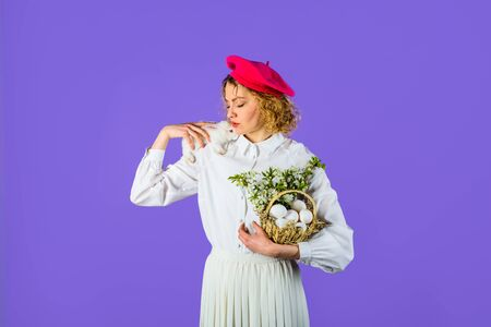 Charming adorable woman in beret with Easter basket and Easter bunny rabbit. Stylish woman in headdress holds white little bunny. Stock Photo - 128876288