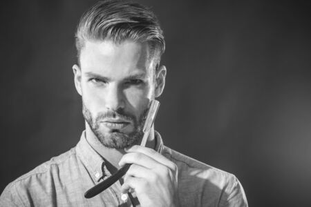 Handsome bearded guy holds dangerous razor near face. Barbershop accessory.