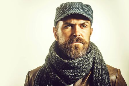 Handsome man wearing demi-season clothing. Advertise autumn-winter fashion. Trendy look. Casual bearded man in jacket, scarf and cap. Male winter fashion. Fashionable handsome bearded man in hat