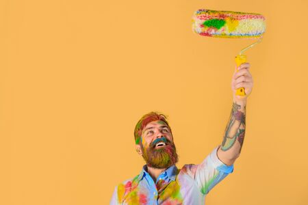 Painter at workplace. Repair, building, home renovation. Happy bearded man with painting roller. Interior working. Handsome painter, craftsman in colorful shirt painting wall in room. Making repair. Zdjęcie Seryjne