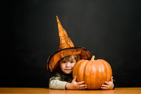 Cute boy in witch hat with halloween pumpkin. Jack o lantern. Preparation Halloween holiday. Boy dressed up trick or treating. Child with pumpkin. Halloween party. Kid trick or treat. Happy Halloween