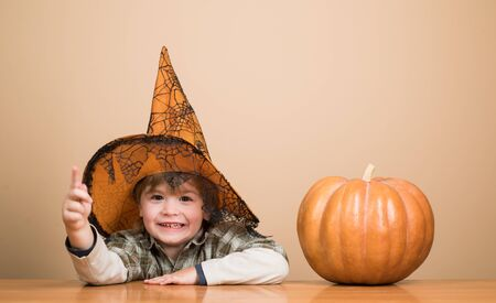Halloween party. Cute boy in witch hat with halloween pumpkin pointing to you. Kid trick or treat. Boy dressed up trick or treating. Preparation Halloween holiday. Child with pumpkin. Happy Halloween Banco de Imagens